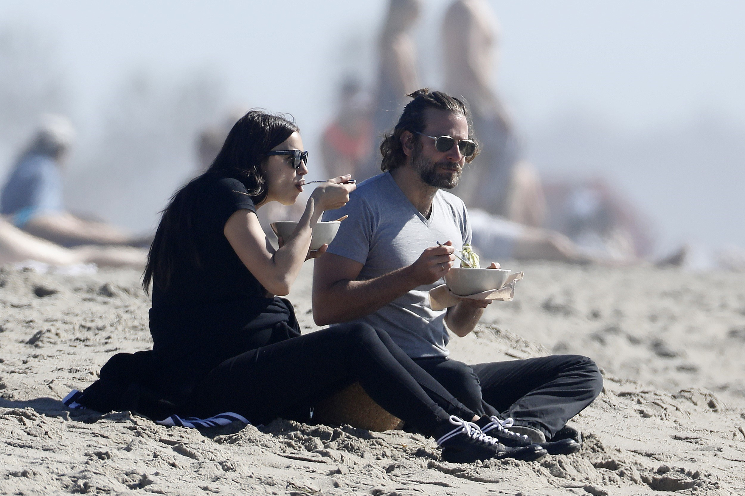 Photo © 2017 AKM GSI/The Grosby Group PREMIUM EXCLUSIVE Los Angeles, February 14, 2017. Bradley Cooper and Irina Shayk bring their own lunch to the beach and cuddle after enjoying their meal. The couple look sweet and in love as Bradley helps Irina stand up so they can leave hand in hand.