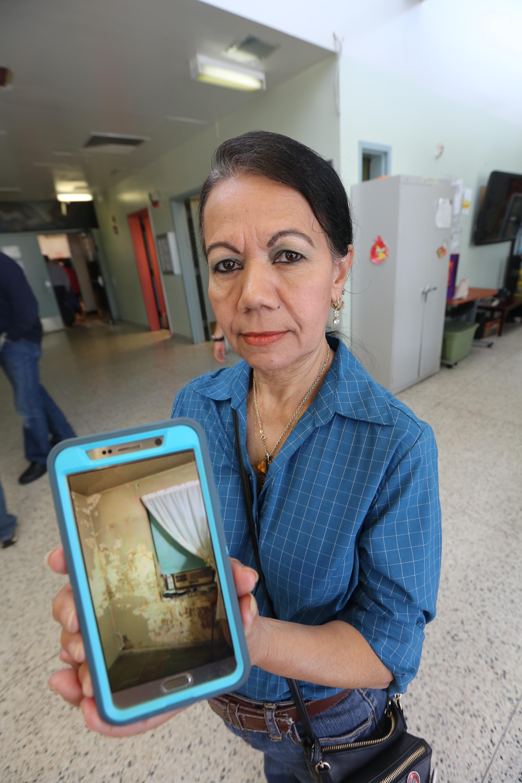Inquilina Juana Narvaez muestra una foto del moho en su celular. Concejales Carlos Menchaca y Ritchie Torres durante una audiencia sobre el moho en los departamentos de NYCHA en Red Hook, Brooklyn.