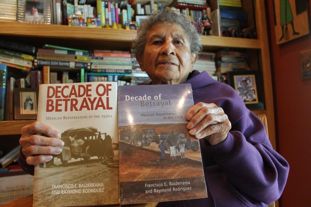 """Emilia Castañeda, de 89 años de edad sostiene el libro """"Década de la traición"""", que habla de la repatriación de mexicanos en la década de 1930."""
