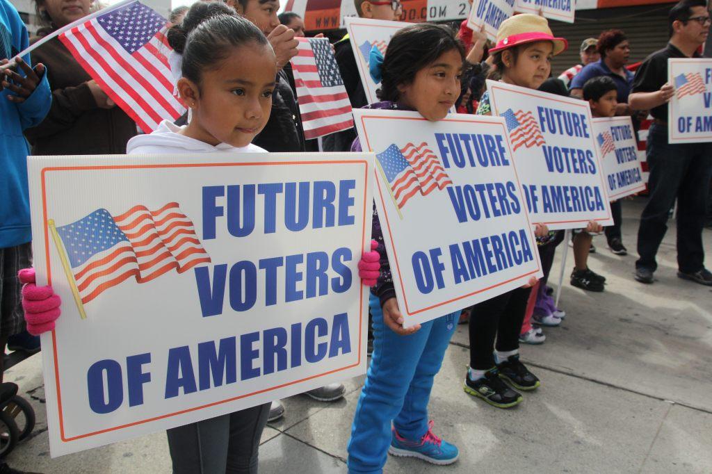 """Un grupo de niños sostiene carteles en donde se lee """"Futuros votantes de América""""."""