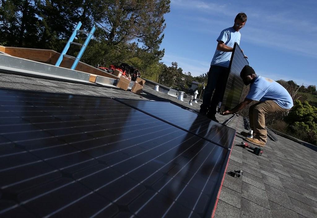 Trabajadores instalan paneles solares en una casa de San Rafael, California. El futuro de la energía verde está en manos de los latinos en California.