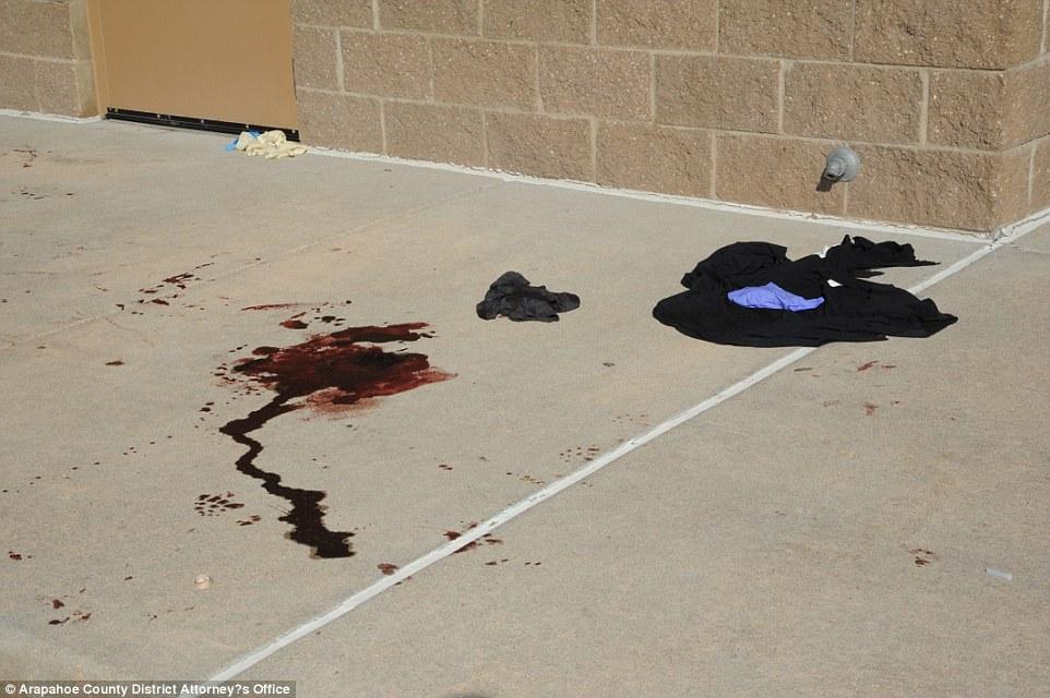 Manchas de sangre de los heridos cubren la acera afuera del cine.