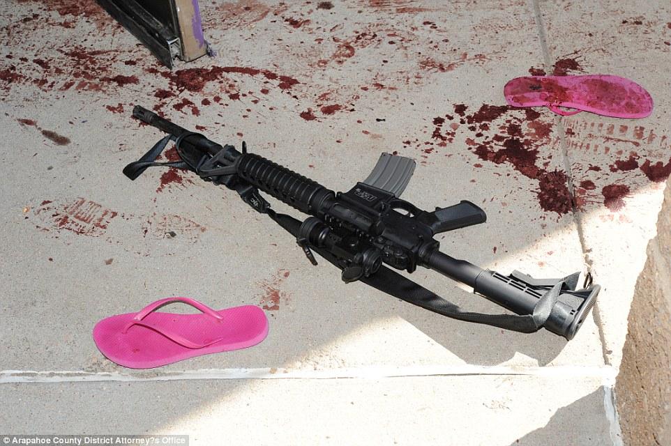 El rifle de Holmes en el suelo afuera del cine, al lado de unas sandalias rosadas, cubiertas de sangre.