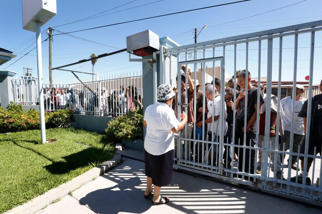 Un centenar de inmigrantes deportados esperan recibir una comida gratis en Casa Madre Assunta. /Aurelia Ventura