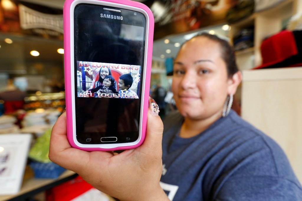 Ilenee Velasco muestra una foto de sus hijos.
