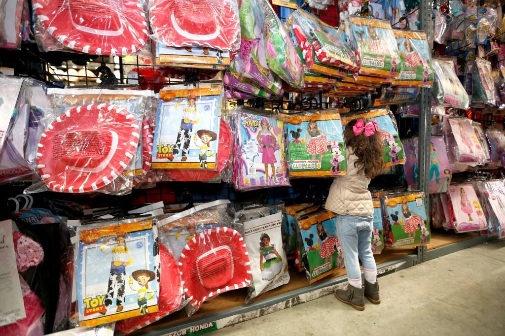 Antonela Pedroza de 3 años revisa los atuendos para niñas en la tienda Halloween Club.