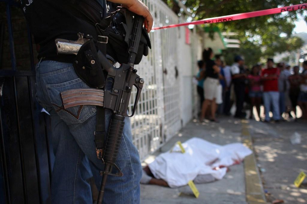 Un policía observa la escena de un crimen relacionado al narcotráfico en Acapulco en el 2012. / Getty