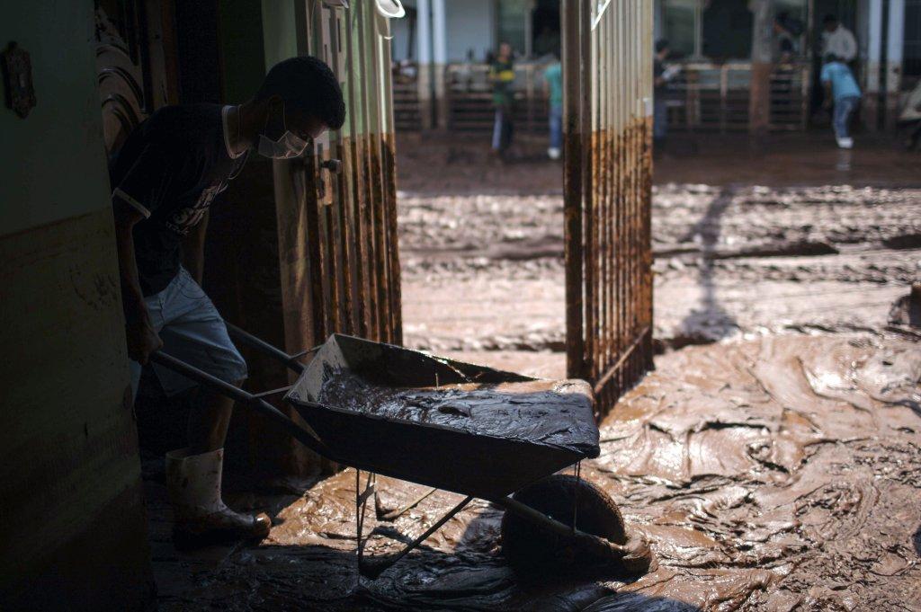 Un hombre intenta limpiar su casa anegada por el lodo de una mina de la empresa Samarco, en Mariana, Minas Gerais.