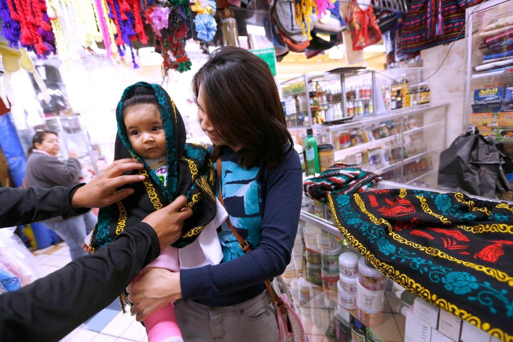 La salvadoreña Zulma López y su esposo, el mexicano Arturo Panales, llevaron a su niña de 9 meses a comprarle su vestido de indígena. /AURELIA VENTURA