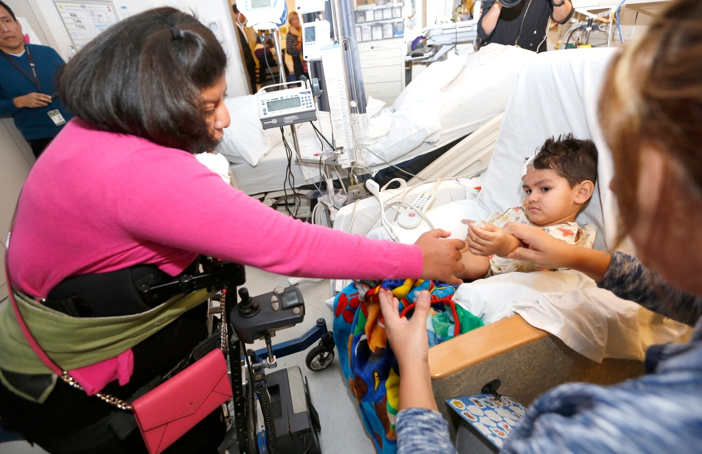 12/14/15 /LOS ANGELES/Formerly conjoined Guatemalan twins Josie (L) and Teresita Alvarez return to Mattel Children's Hospital to visit and give the gift of Christmas joy to 2 year-old Giovanny Hernandez. Guatemalan twins Josie and Teresita Alvarez returned to the medical staff who helped separate them in 2002.  (Photo by Aurelia Ventura/La Opinion)