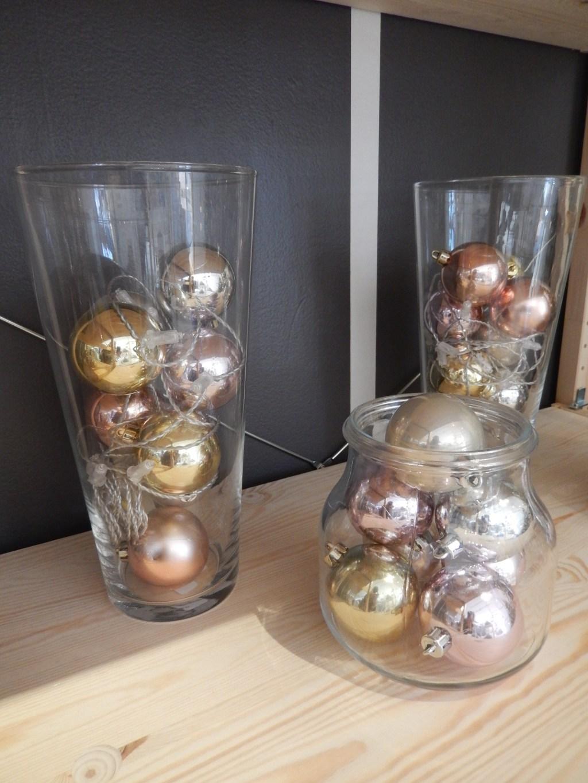 Los floreros altos y en forma cilíndrica se prestan para llenarlos de esferas rosadas, doradas y plateadas.