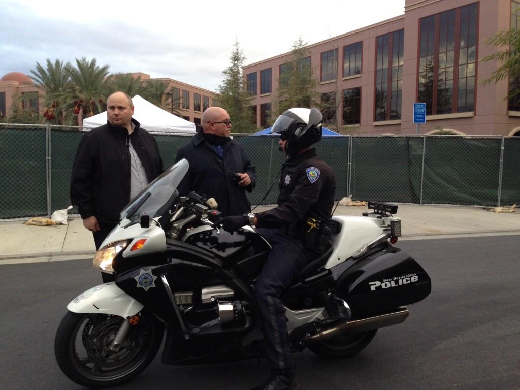 Un policía en moto conversa con guardias privados afuera del Centro Regional Inland de San Bernardino