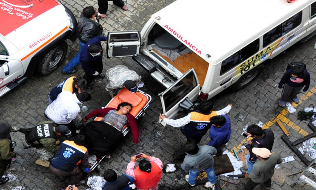 Policías y rescatistas transportan a una mujer herida tras un incendio provocado por manifestantes eb El Alto, Bolivia.