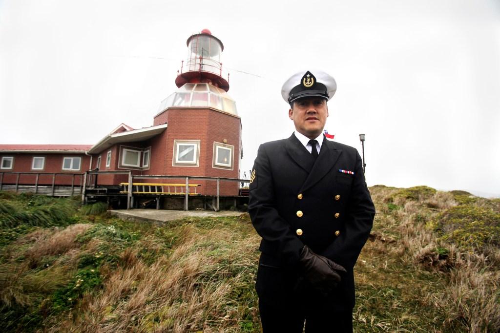 El sargento de la Armada de Chile José Aguayo posando junto al faro ubicado en la Isla de Cabo de Hornos.