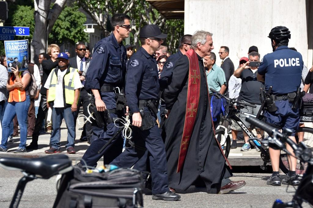 Policías detienen al religioso Chris Ponnet, del Centro Camillus Católico Romano tras una protesta contra las deportaciones, en Los Ángeles, California.