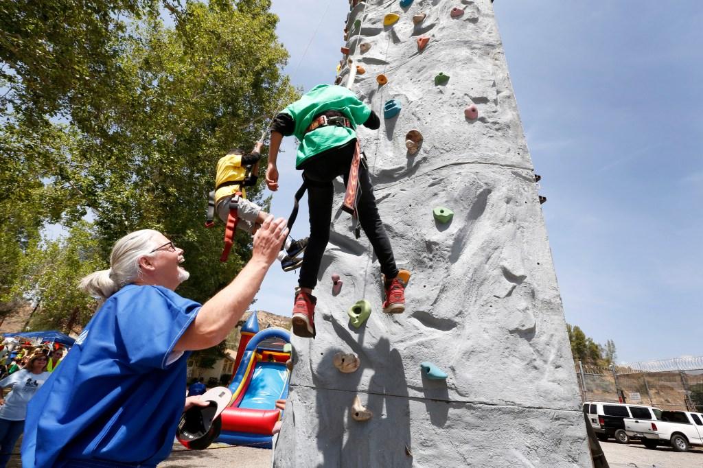 Tony Haschke ayuda a sus nietos Michael López, de 8 años, y Aden, de 7 años, a escalar una roca durante el evento de presos con hijos y nietos. (Foto:Aurelia Ventura/ La Opinion)