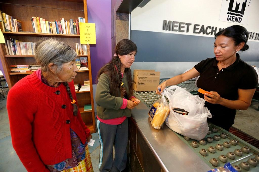 Amelia López y su madre, Elizabeth López, recogen alimentos en la asociación no lucrativa MEND. (Aurelia Ventura/La Opinion)