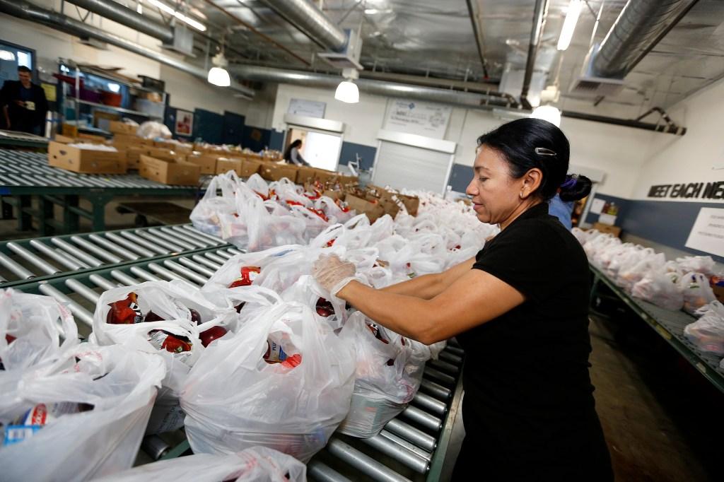 Danubia Alarcon, voluntaria de MEND, ayuda a preparar bolsas de comida para distribuir entre personas necesitadas. (Aurelia Ventura/La Opinion)