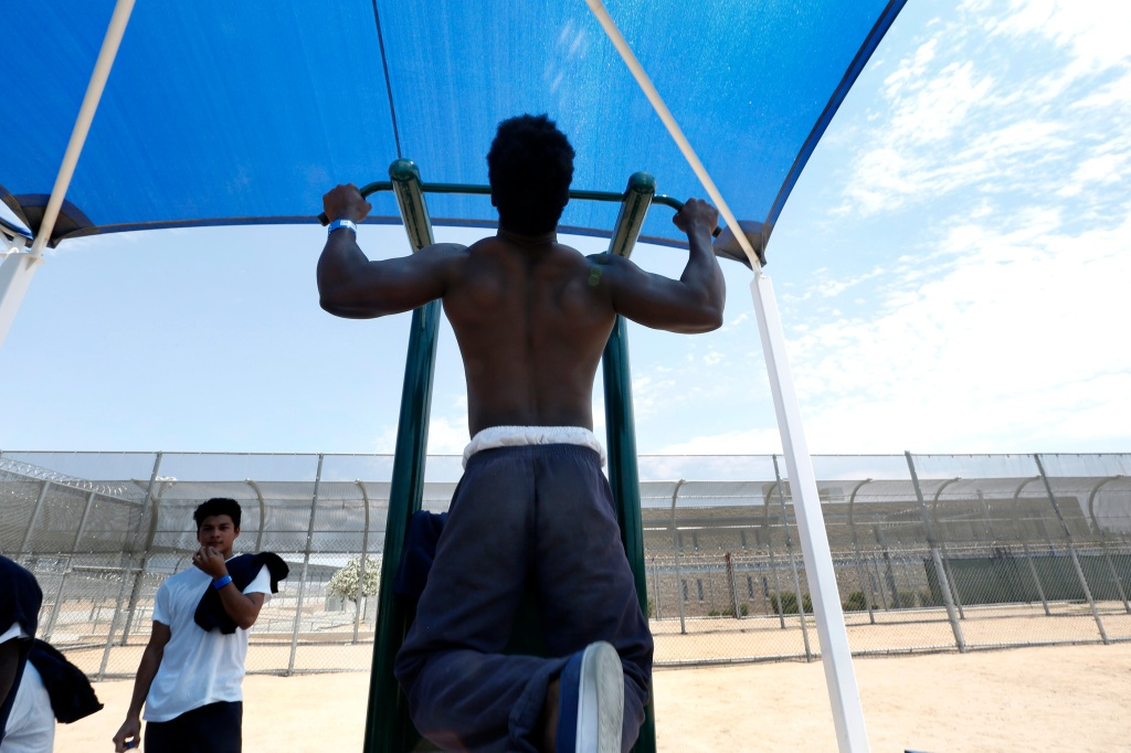 06/21/16/ ADELANTO/Detainees work out in the yard behind double fencing and barbed wire at the Adelanto Detention Center. The facility, the largest and newest Immigration and Customs Enforcement (ICE), detention center in California, houses males and females an average of 1,700 immigrants in custody pending a decision in their immigration cases or awaiting deportation. (Photo Aurelia Ventura/ La Opinion)