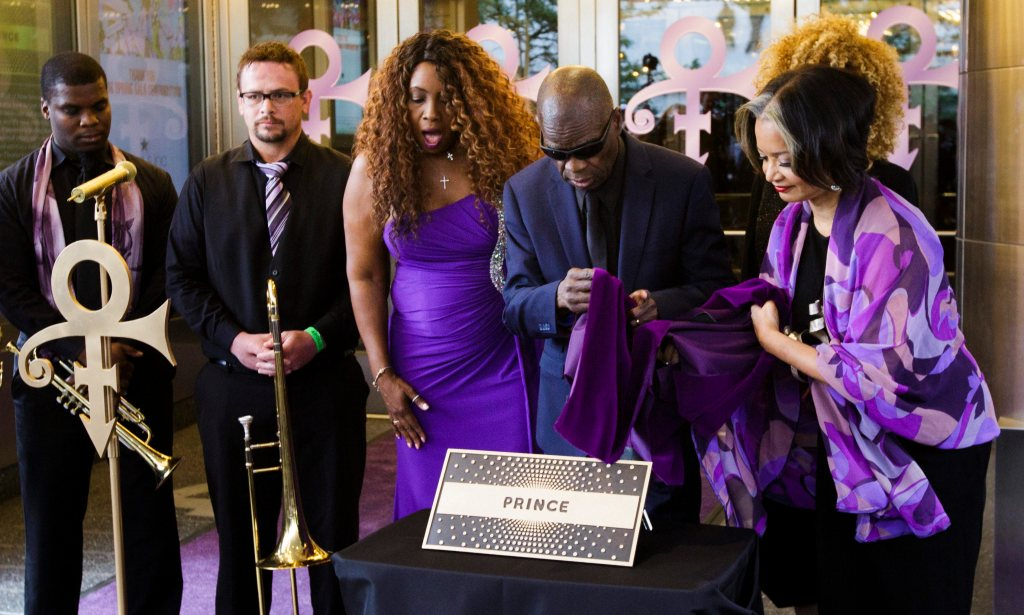 Los músicos Mel'sa Morgan (3-i), Maceo Parker (4-i), Jonelle Procope (d), directora ejecutivo del teatro Apollo, y los integrantes de New Power Generation de Prince (i) al artista estadounidense Prince al Paseo de la Fama del teatro Apollo