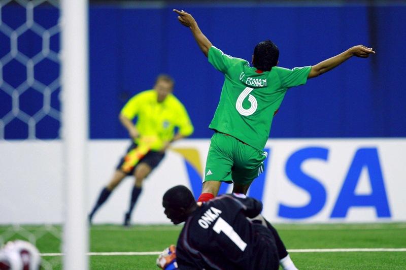 Omar Esparza de la selección mexicana Sub 20 festeja un gol al Congo mientras el portero Destin Onka yace en el pasto. La foto es del Mundial Sub20 de 2007 realizado en Canadá.