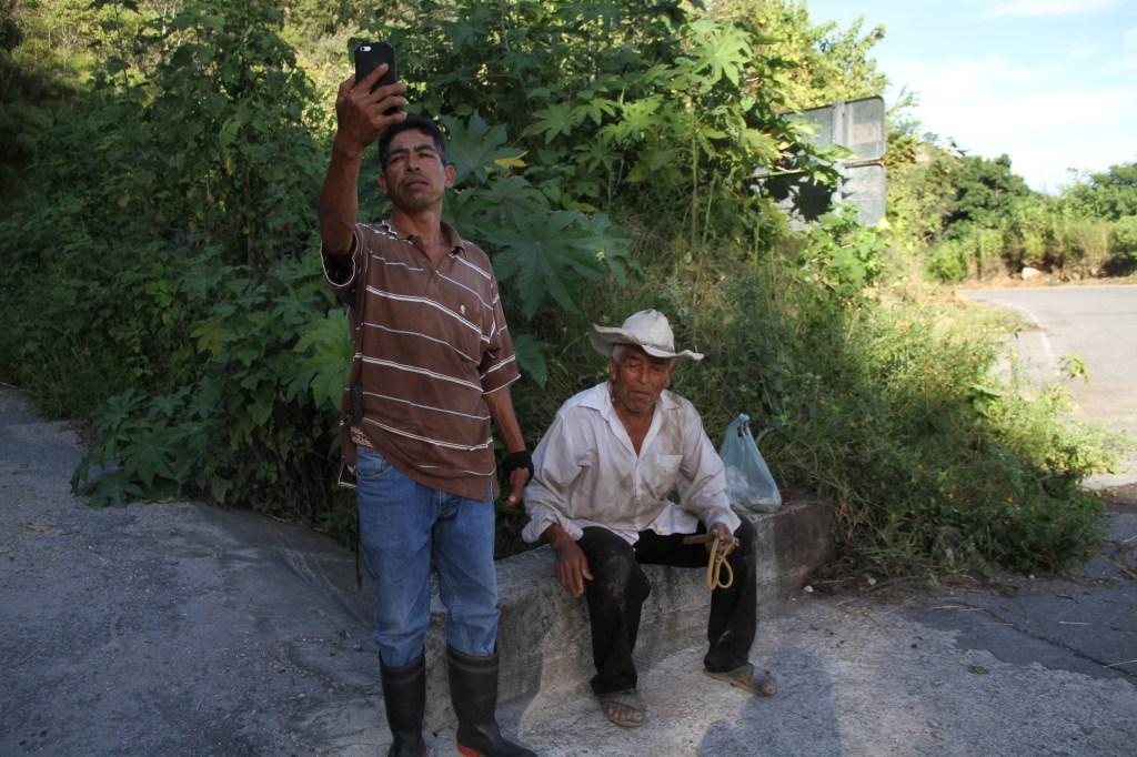 Ángel Morales López busca señal de internet mientras su padre espera que lo acompañe a pastorear los chivos.