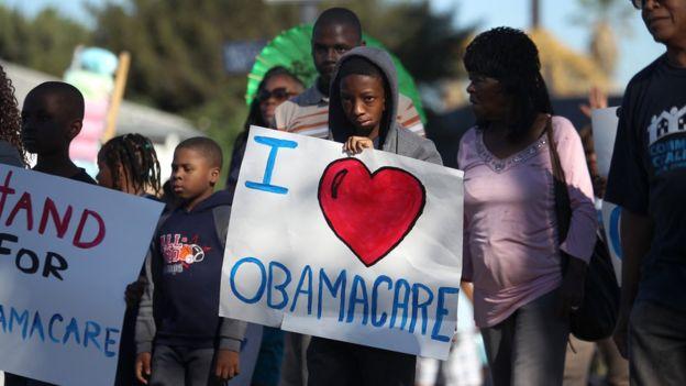 """Niño con cartel a favor del ObamacareImage copyrightGETTY IMAGES Image caption El """"Obamacare"""" ha recibido críticas por parte de los conservadores estadounidenses. Getty"""