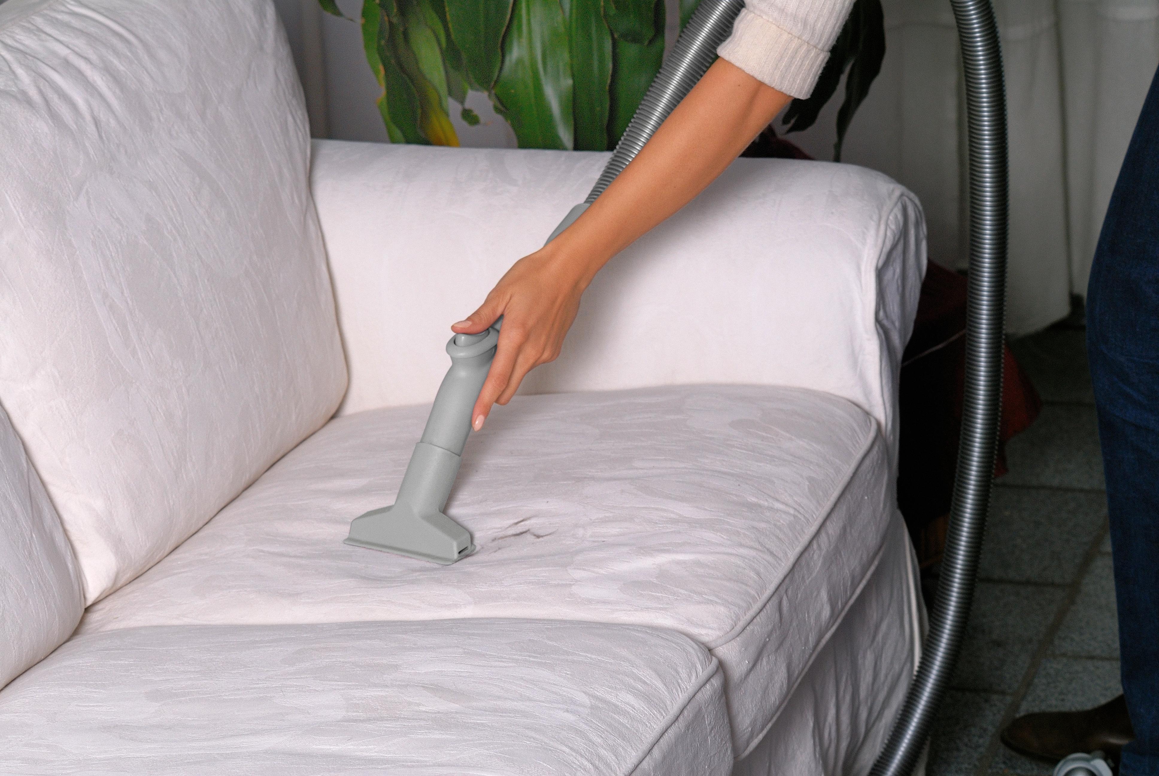 Además de pasar la aspiradora por la parte superior de los cojines del sofá, levántalos y aspira toda la base del mueble.