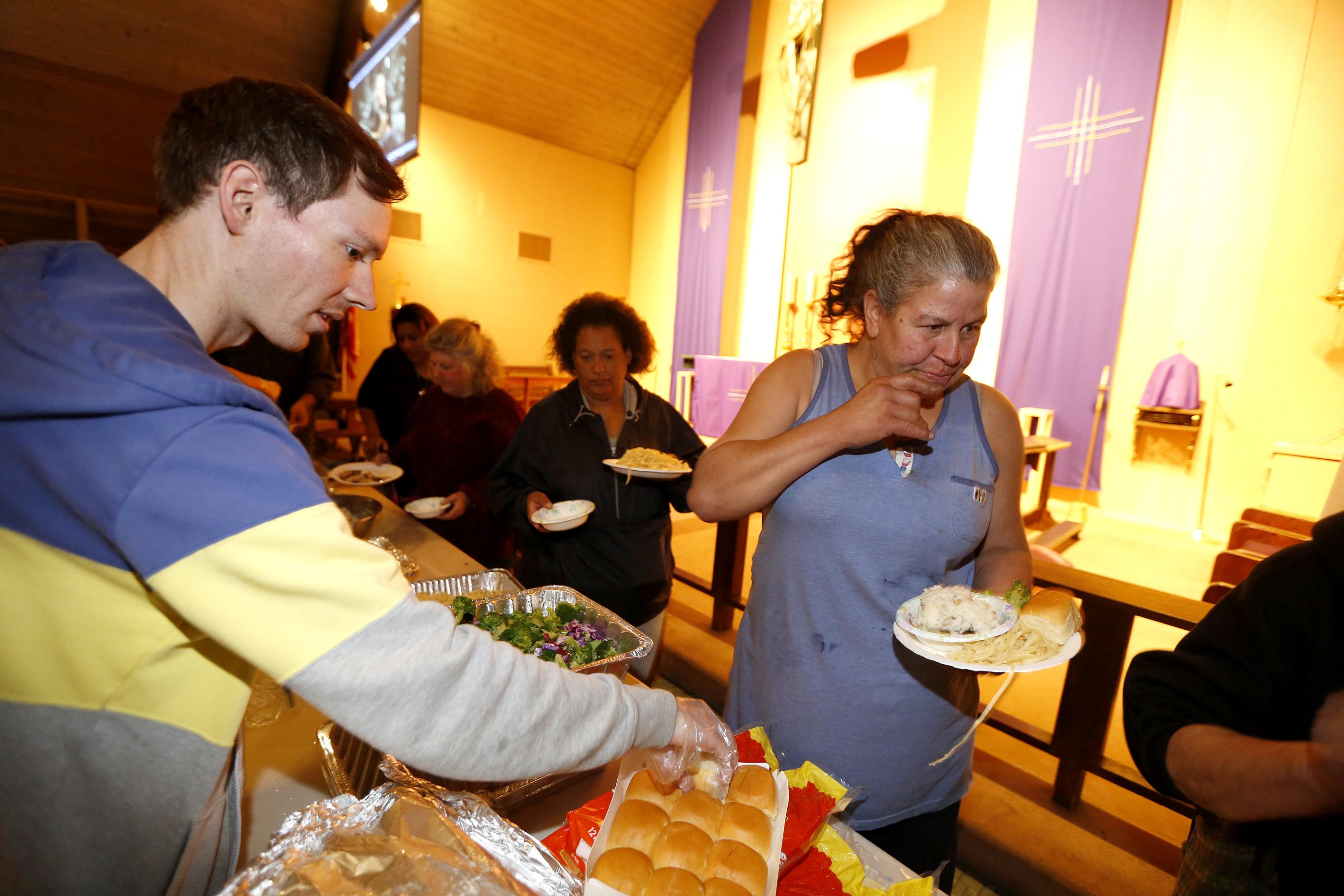 Voluntarios ofrecen comida a los desamparados que llegan al refugio. (Aurelia Ventura/ La Opinion)