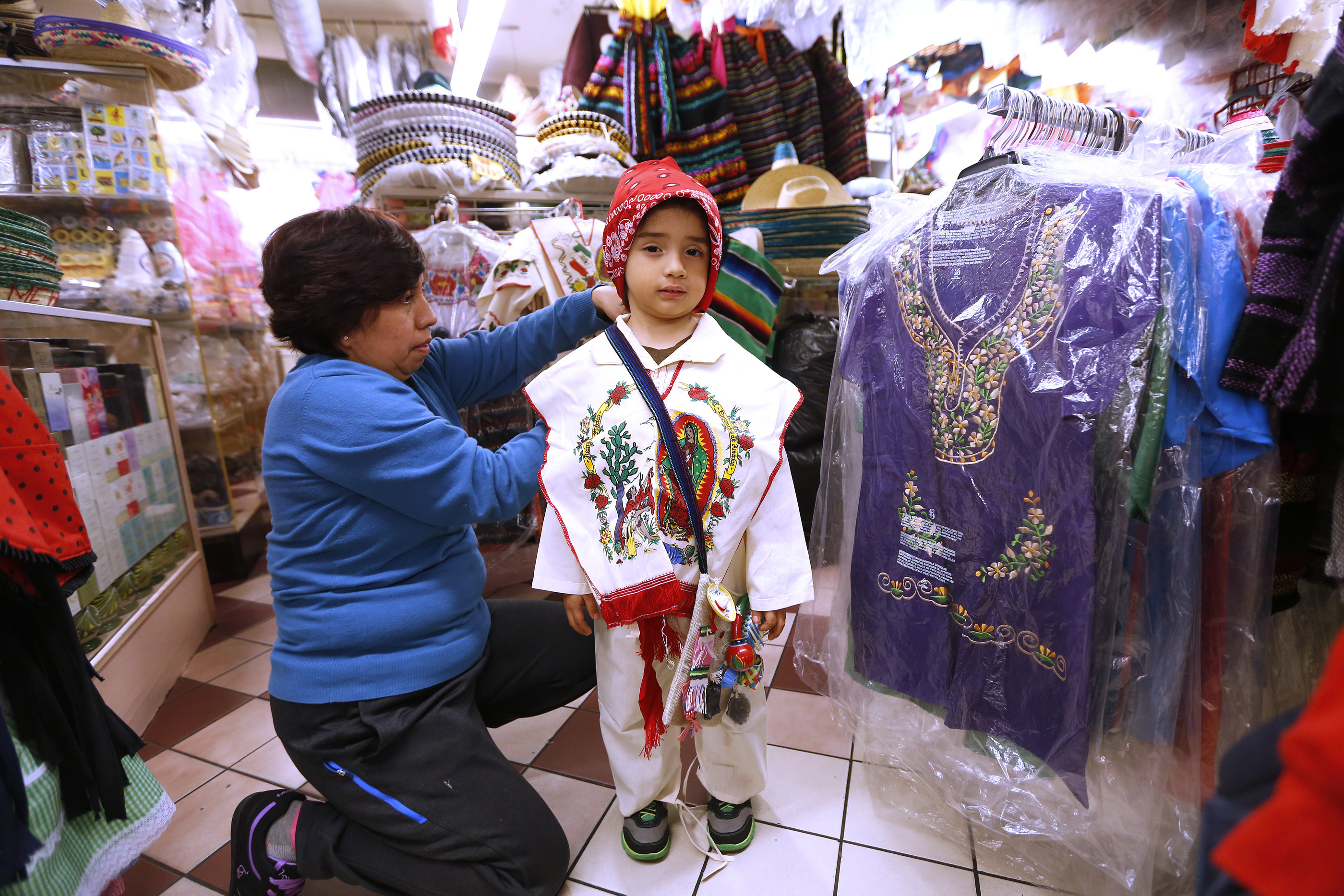 12/09/16 /LOS ANGELES/5 year-old Joshua Jimenez with his grandmother Mary Teresa Jimenez, from Thousand Oaks, tries on an outfit while shopping at the popular Mercadito in East Los Angeles. Hundreds of religious Catholics will be celebrating the Virgin of Guadalupe. (Photo by Aurelia Ventura/La Opinion)