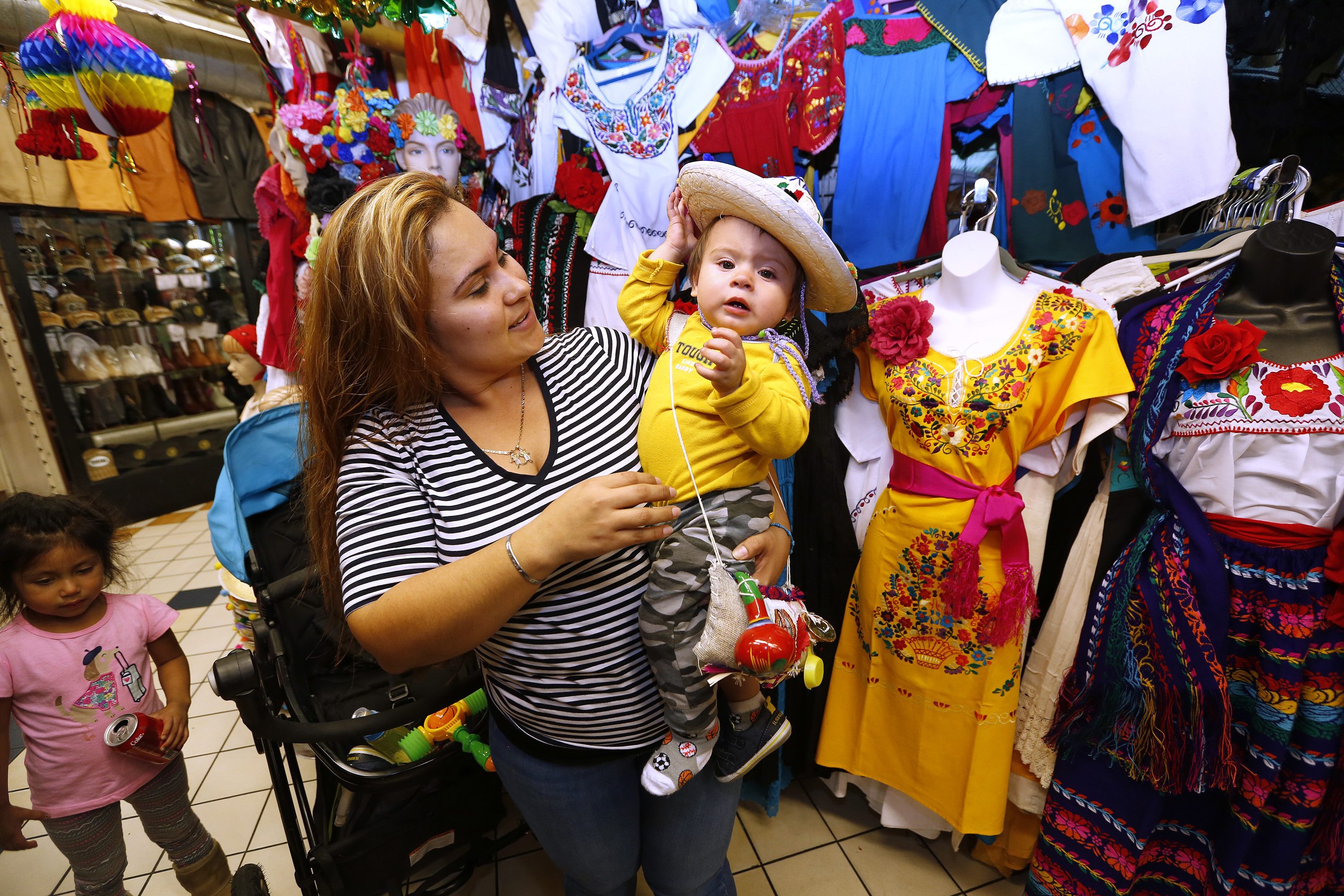 12/09/16 /LOS ANGELES/1 year-old Cesar Mateo with mom Guadalupe Erenas tries on an outfit while shopping at the popular Mercadito in East Los Angeles. Hundreds of religious Catholics will be celebrating the Virgin of Guadalupe. (Photo by Aurelia Ventura/La Opinion)