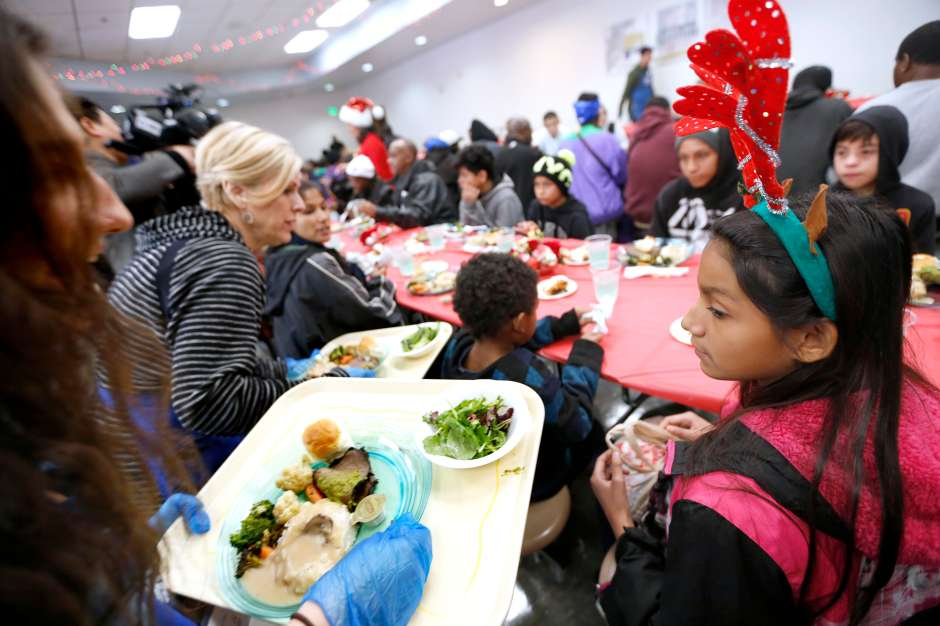 12/23/16 /LOS ANGELES/12 year old Haven Pimienta with her family is served a Christmas meal during the Los Angeles Mission Christmas Eve event in Skid Row. The Los Angeles Mission Christmas Eve event offered a 2000 square foot winter wonderland tent where Santa Claus distributed thousands of toys and goodies to needy children. A holiday feast was served to approximately 3,000 people. (Photo by Aurelia Ventura/La Opinion)