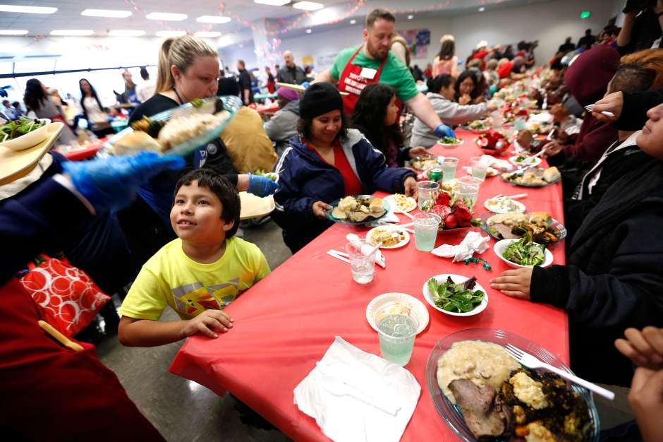 12/23/16 /LOS ANGELES/6 year old Moses Sanchez with his family is served a Christmas meal during the Los Angeles Mission Christmas Eve event in Skid Row. The Los Angeles Mission Christmas Eve event offered a 2000 square foot winter wonderland tent where Santa Claus distributed thousands of toys and goodies to needy children. A holiday feast was served to approximately 3,000 people. (Photo by Aurelia Ventura/La Opinion)