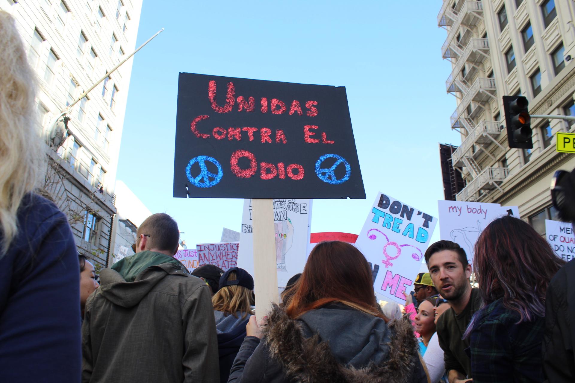 Ana Flores, de 24 años, marcha de la mano de su compañera para pedir se respeten los derechos de inmigrantes y de la mujer. (Foto: Joanna Jacobo/La Opinión)