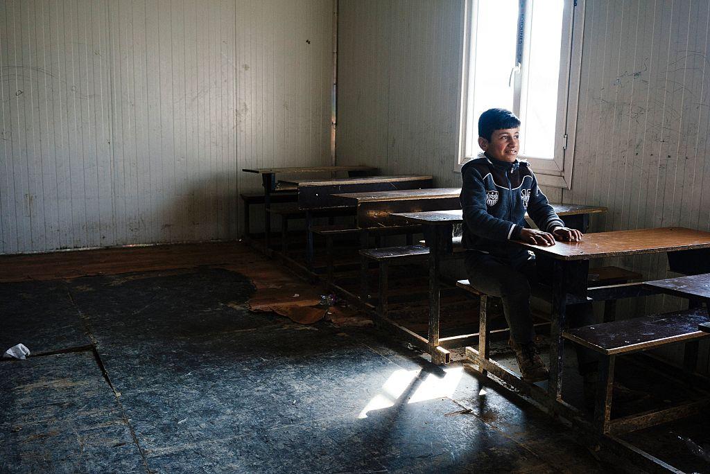 Un niño se sienta en pupitre en una escuela de Mosul.