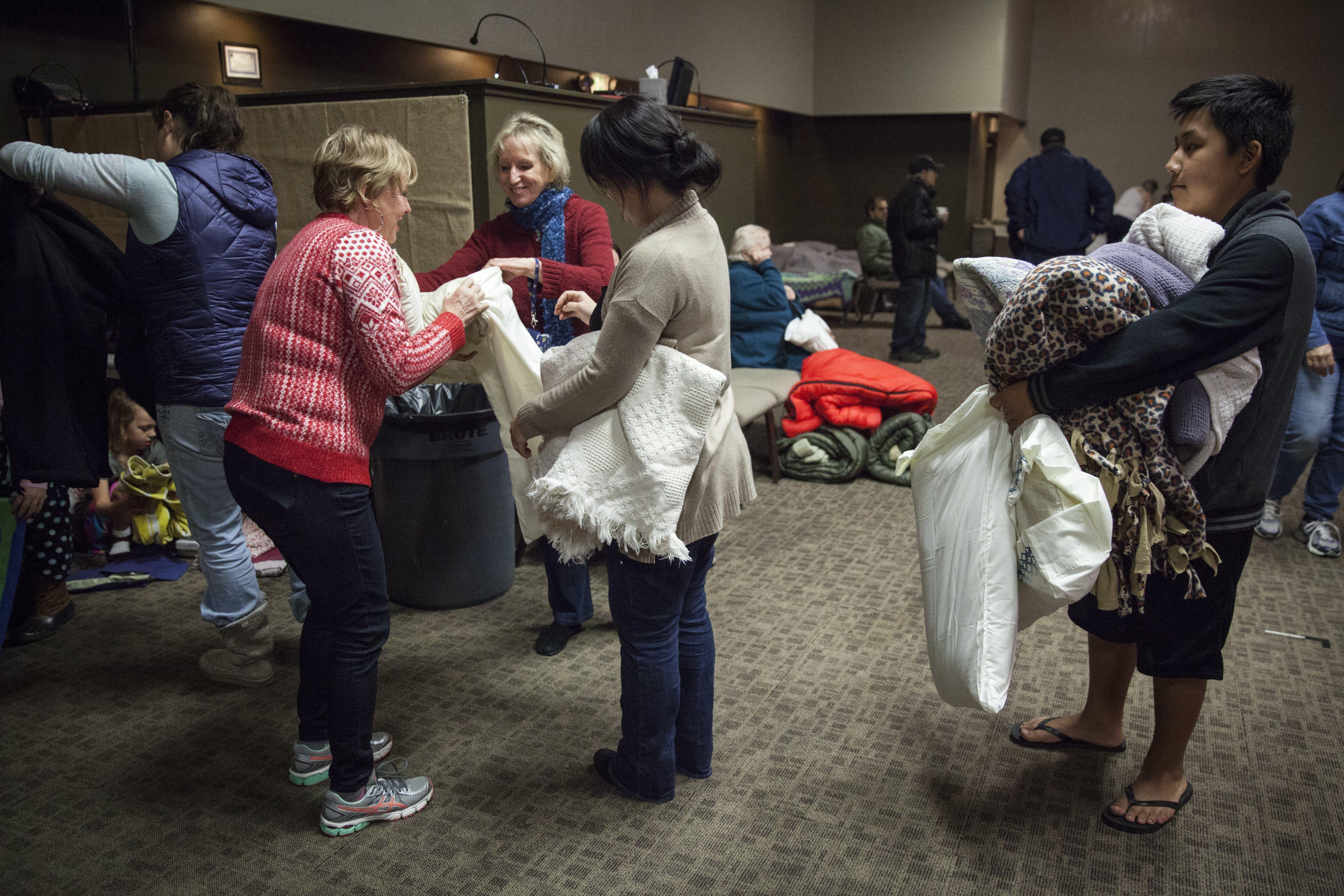 Voluntarios reparten mantas entre los vecinos en un centro de evacuación en el barrio de Church of Chico, en Chico, California (Foto: EFE)