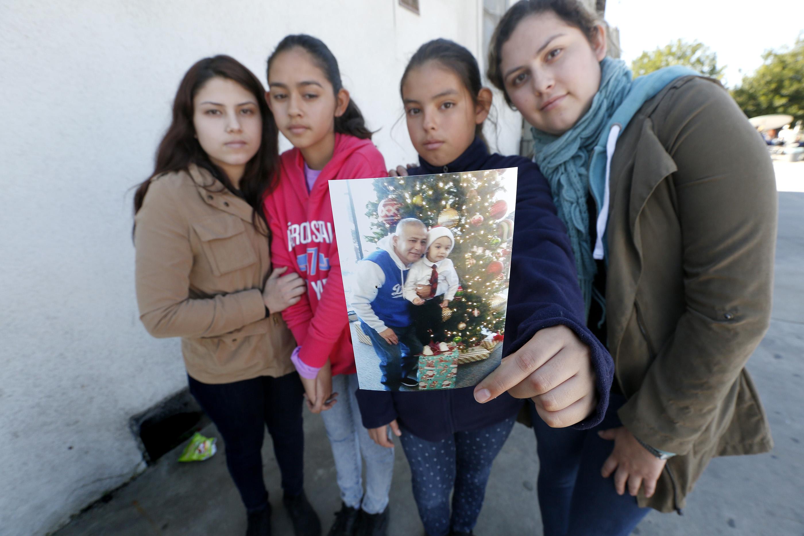 Brenda Avelica, de 24 años, junto a sus hermanas menores, Joselyn, de 19, Fatima de 13, y Yuleni, de 12, muestran una foto de su padre, Romulo Avelica, detenido mientras llevaba a sus hijas a la escuela. (Aurelia Ventura/La Opinion)
