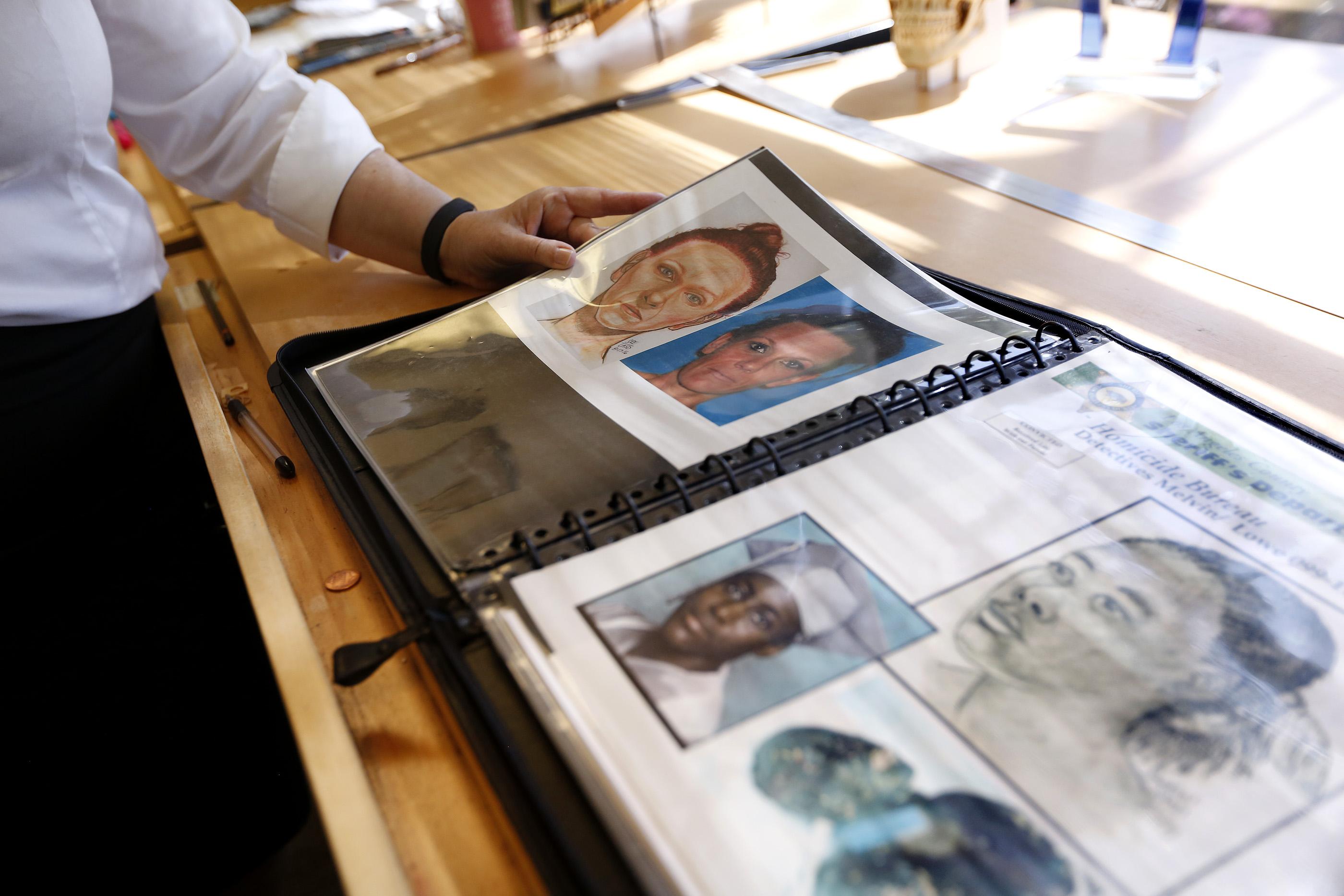 Sandra Enslow, coordinadora de artes gráficas para el Sheriff, muestra bocetos de investigaciones famosas que ha realizado el Departamento del Sheriff. (Aurelia Ventura/La Opinion)