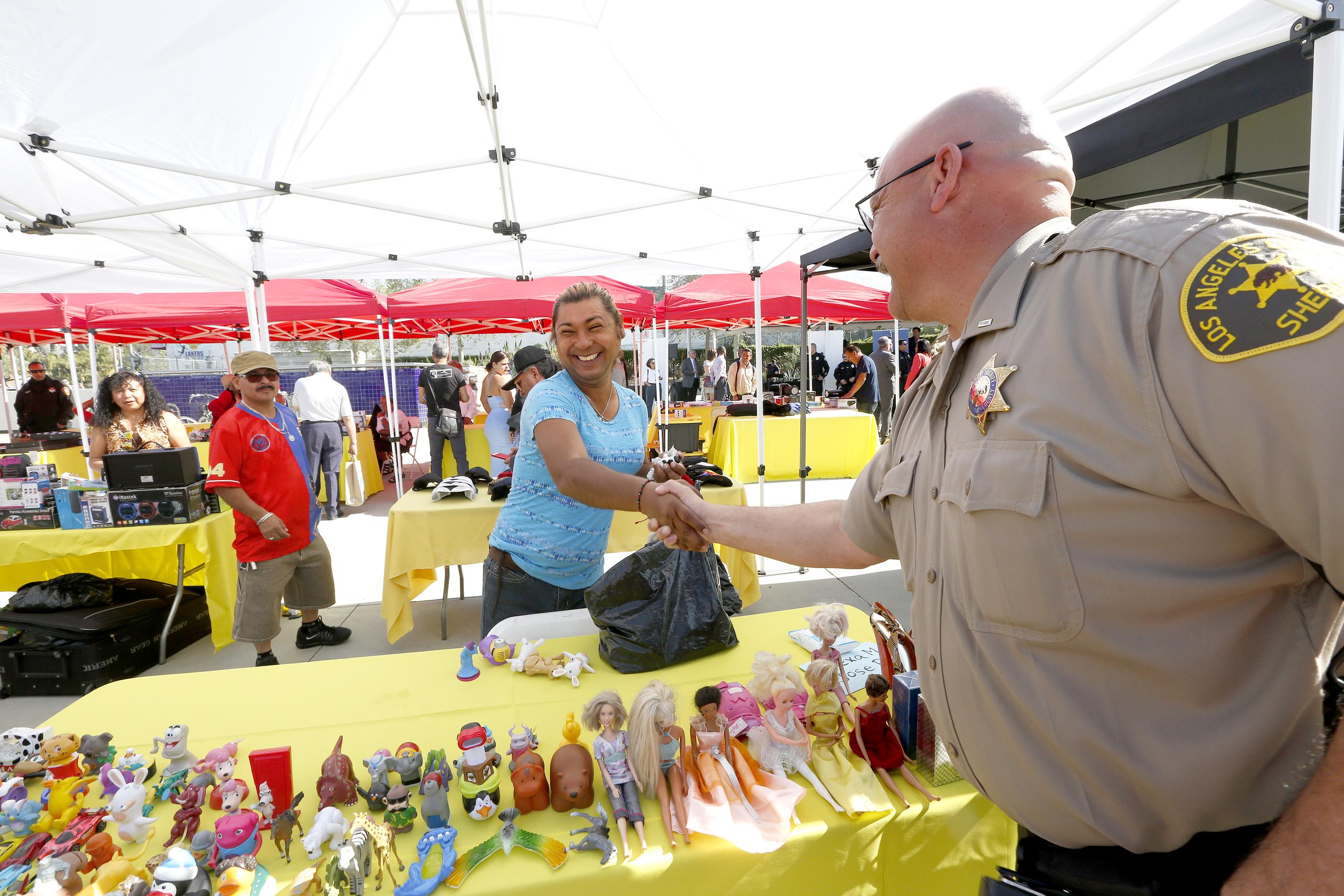 El Tte. Henry Saucedo saluda a la vendedora Alexa Montero durante la aperture del mercado comuntiario. Habra vigilancia y mayor presencia policial en el lugar. (Aurelia Ventura/La Opinion)