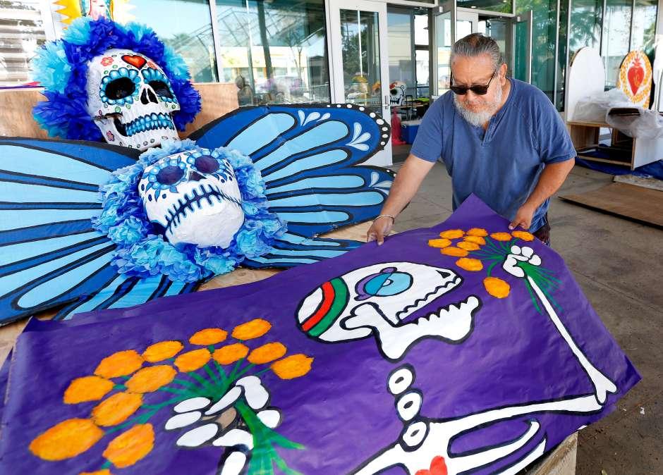 El artista Manny Velásquez muestra piezas de arte para la celebración del Día de los Muertos en Pacoima. (Aurelia Ventura/ La Opinion)