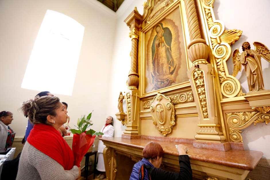 Feligreses oran frente a una imagen de la Virgen de Guadalupe dentro de la iglesia La Placita. (Aurelia Ventura/ La Opinion)