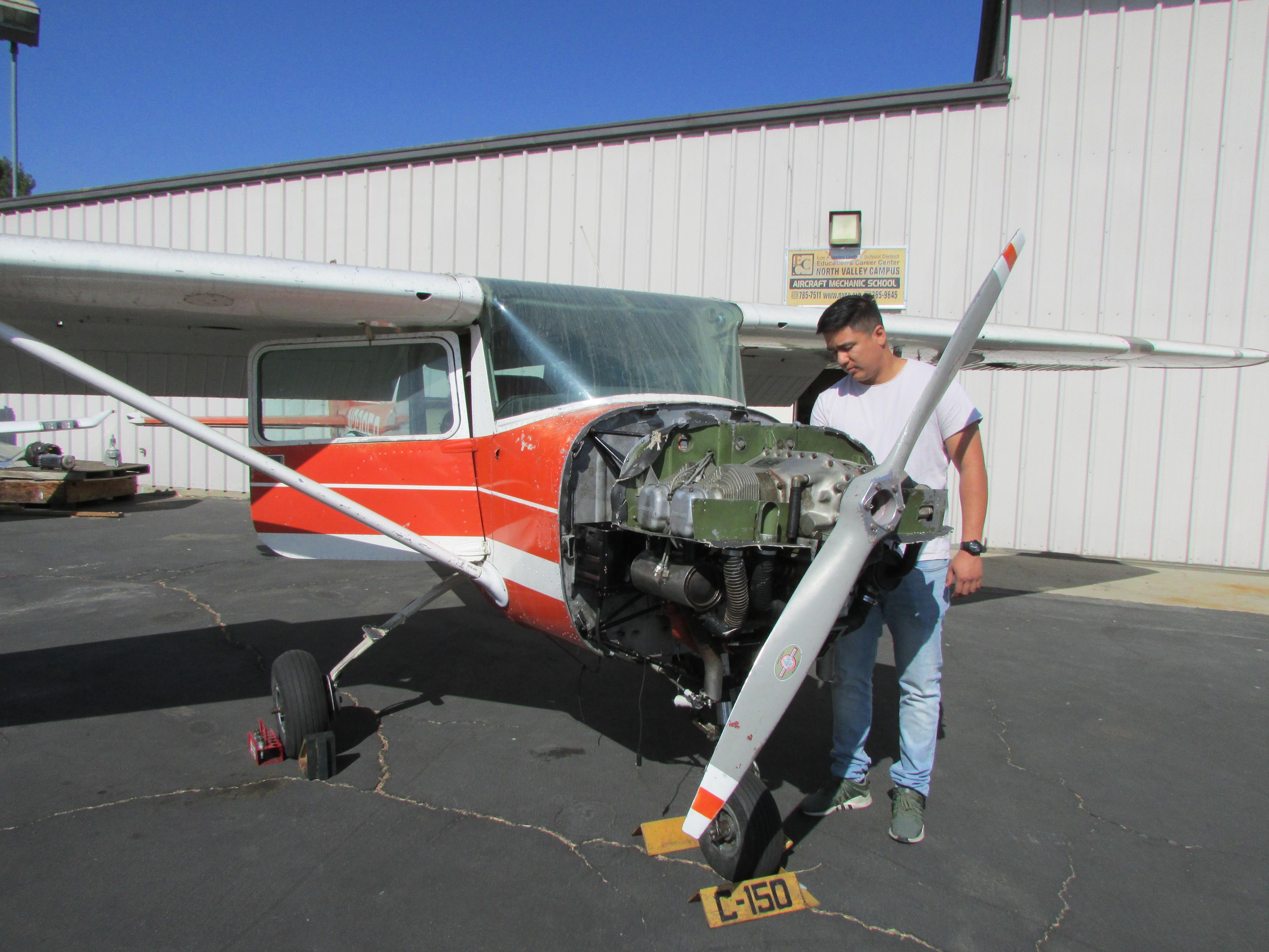 Edgardo Vásquez revisa bien uno de los aviones donde ha aprendido a ser mecánico de aviación. (Araceli Martínez/La Opinión).