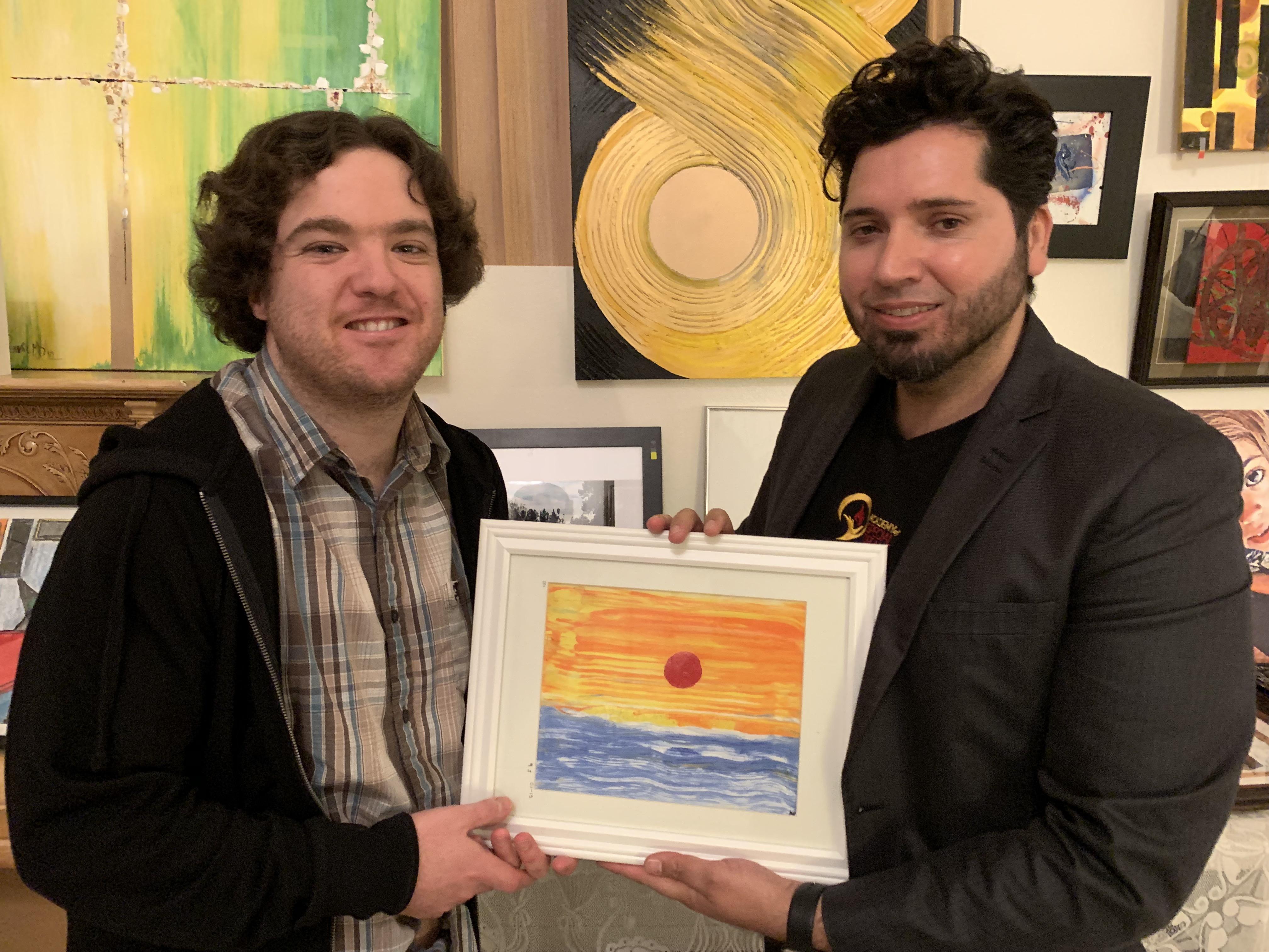 Mike sostiene una pintura que exhibió en el bazar de New Art Gallery de Silvia Villegas en beneficio de la Academia de Sueños Especiales creada por Michael Dergar. (Araceli Martínez/La Opinión).